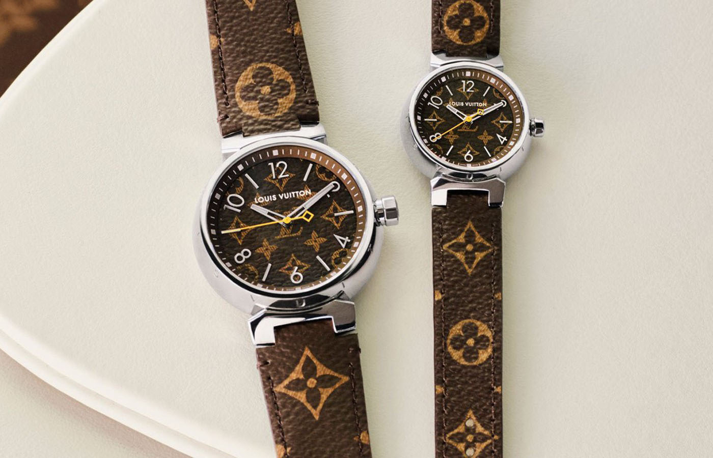 """时间回到2002年,路易威登携Tambour初涉制表领域,这是一款前所未见的腕表,将品牌所有价值融入设计中:12个""""Louis Vuitton""""字母镌刻在表壳上,对应12个小时时标,棕色表盘灵感源自著名的Monogram,而黄色秒针则让人联想到路易威登箱包的蜡线。  Tambour提供多种型号——从简单三针石英款式到高度复杂功能版本——结合隽永外观和不断升级的技术性能,已经成为象征身份的标志。如今,路易威登为Tambour系列再添两款全新Monogram型号。  紧随其后,路易威登还将发布全新Tambour Damier Graphite腕表。日内瓦La Fabrique du Temps工坊的表盘专家凭借精湛技艺,将经典表壳与全新表盘完美融合,忠实再现Monogram和Damier Graphite帆布的设计魅力。  全新Tambour Monogram腕表内置石英机芯,为时分秒显示功能提供动力。新款腕表采用精钢表壳,分为28毫米、34毫米和39.5毫米三种尺寸版本。抛光镀铑时分指针涂覆Superluminova荧光物料,秒针则以传统的黄色装饰。表盘镌刻和印刷Monogram图案,表带由Monogram帆布制成,并配有Ardillon表扣。表带应用路易威登发明的专利替换系统,佩戴者可以自由搭配,完美适应任何场合,并且展现独特个性。"""