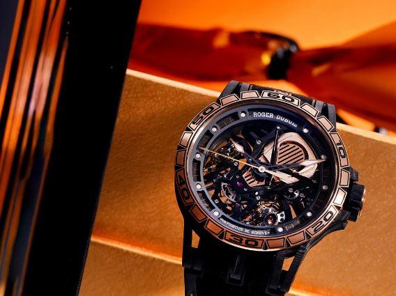 """新款罗杰杜彼Excalibur Aventador S系列玫瑰金腕表延续了以88枚限量版形式推出的前身""""Giallo Orion""""(黄色猎户座)的表款经典设计,配备相同的复层碳纤维镂空表壳,再现此枚腕表的独特美学。此款腕表仅限28枚。官方型号:RDDBEX0654  腕表中央为一个犹如超跑配备的动能储存显示器,其造型仿佛一个透明""""引擎盖"""",是整款腕表之中最具标志性的设计,给人留有深刻印象。  镂空表盘的黑色边缘,搭配覆有白色SLN夜光涂料的玫瑰金刻度,与中央黑色PVD涂层18K金指针相呼应,令时间指示更加清晰直观。此外,表针的针头部分亦填充有色SLN夜光涂料,即使在较暗的环境下也能够观察时间。  此款独特时计配备着带有差速器的双摆轮游丝——两者皆以45度角摆设,且横跨着机芯设置了「引擎室拉杆」。装饰18K玫瑰金镂空指针,与玫瑰金表圈相融。玫瑰金的温暖色泽与腕表各部位产生优美的对比映衬。"""